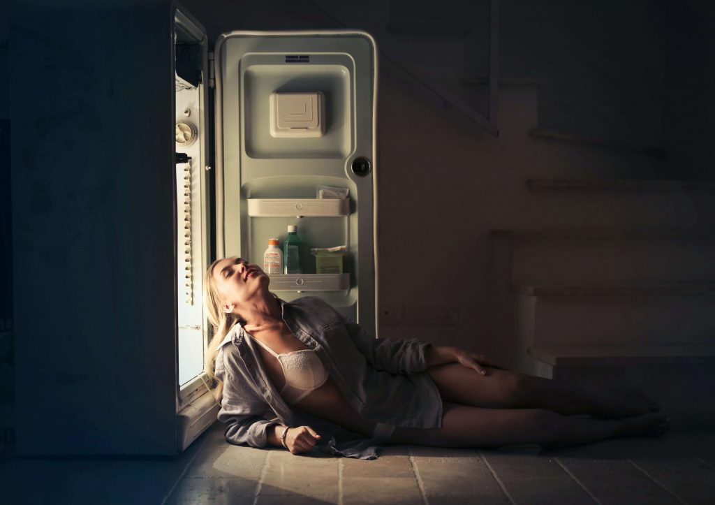 woman cooling down next to open refrigirator